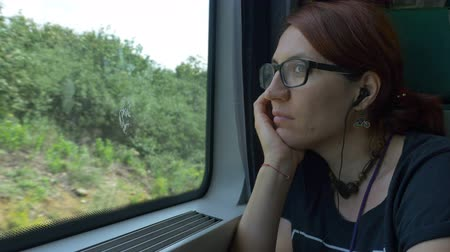 Girl with eyeglasses and earphones looking through train window while travelling.