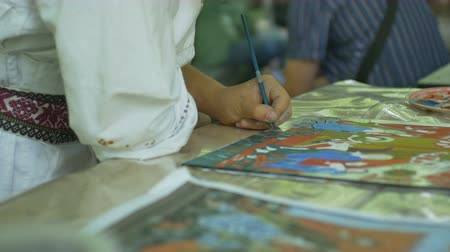 antiques : Artisan is painting a religious themed icon on glass.