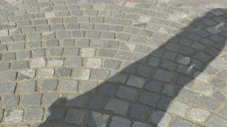 çini : View of a walking shaddow of girl on cobblestone road.