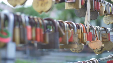 hűség : View of some love locks on a bridge standing in rain. Stock mozgókép