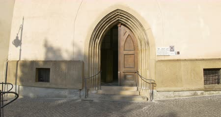 Entering a Catholic medieval Gothic arcade portal church door. Stok Video