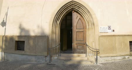 Walking towards the gothic doors of old church.