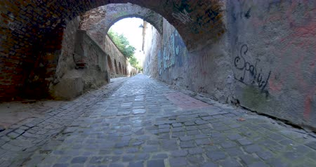 ghetto streets : Walking on cobblestone under arches and brick walls in a medieval town. Stock Footage