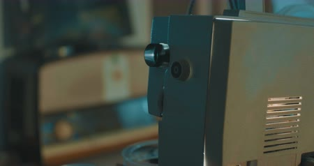 videocamera : View of a vintage projector working in dark room with Super 8 mm film.