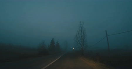 View  of ridding by car on misty night road.