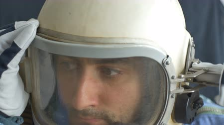 шлем : Dark-haired male astronaut close his helmet window.