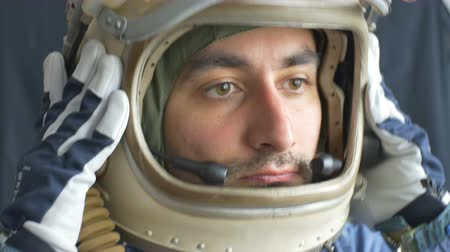velitel : Vintage cosmonaut puts his helmet on head.