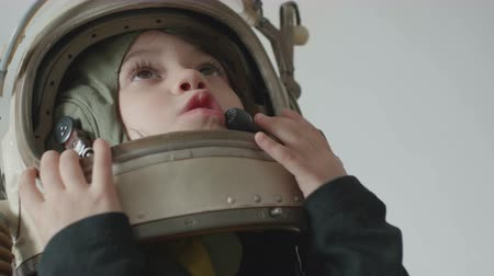 Little cosmonaut girl is looking up towards the stars.