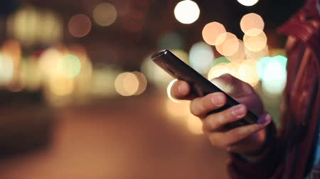 Man sms texting using app on smart phone at night in city. Close up Stock Footage