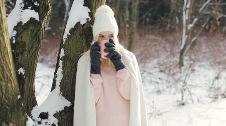 zmrazit : Young beautiful blonde girl in in warm clothes standing near the tree and drinking hot beverage from the pink cup. Dostupné videozáznamy