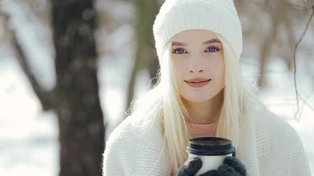 gündelik kıyafetler : Young attractive blonde girl in in warm clothes standing near the tree with the paper cup.