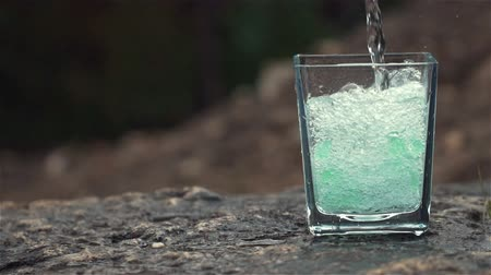glass of fresh water with waterfall in the background Stock Footage