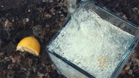 100fps Slow Motion of Sparkling Water and Lemon Falling into Glass. Close up