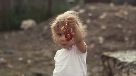 A beautiful little blond girl with curly hair showing her hands with grape to the camera and hides them . Slow motion shot at 100fps