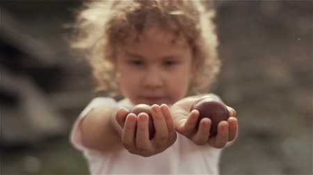 A beautiful little blond girl with curly hair showing her hands with plums to the camera . Slow motion Stock Footage