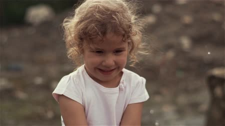 A beautiful little blonde girl with curly hair splashing water into the camera and smiles. Slow motion at 100fps Dostupné videozáznamy