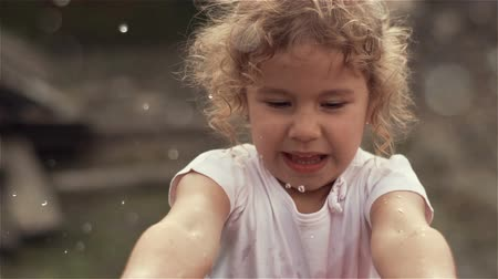 A beautiful little blonde girl with curly hair splashing water into the camera and smiles. Slow motion at 100fps Stock Footage