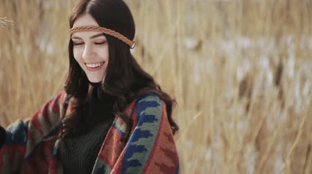 Beautiful dark-haired girl hippie posing on camera on background of dry reeds.