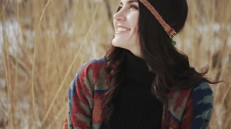 A beautiful dark haired girl hippie poses and smiles at the camera on a background of dry reeds.