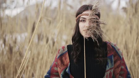 Portrait of a hippie-style Boho girl with a dry reed in her hands.