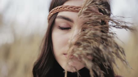 Close-up portrait of a hippie-style Boho girl with a dry reed in her hands. Stock Footage