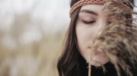 hippi : Close-up portrait of a hippie-style Boho girl with a dry reed in her hands. Stock mozgókép