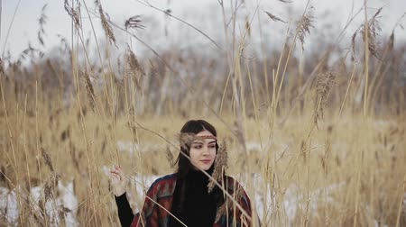 Beautiful brunette girl hippie among dry reeds on a winter day.
