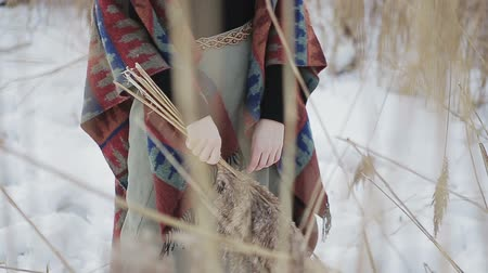 tło retro : Hands of a hippie girl with a bouquet of dried reeds.
