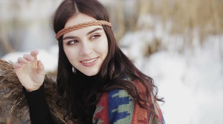 Beautiful brunette girl hippie sits and smiles on a winter day with a bunch of dried reeds in hands on the background of a river.