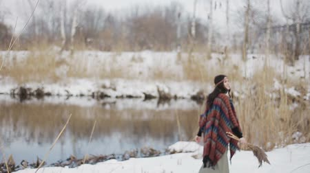 hippi : Beautiful brunette girl hippies walking in a winter day with a bouquet of dry reeds in the hands on the background of the river.
