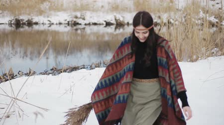 Beautiful brunette girl hippies walking in a winter day with a bouquet of dry reeds in the hands on the background of the river.