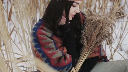 ヒッピー : Beautiful brunette a boho style hippie girl posing on camera on a winter day with a bouquet of dry reeds in hands.