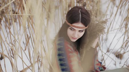 Beautiful brunette a boho style hippie girl posing on camera on a winter day with a bouquet of dry reeds in hands.