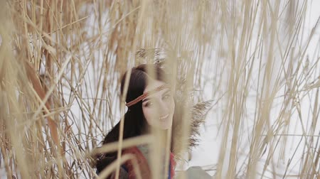 boho : Beautiful brunette a boho style hippie girl posing on camera on a winter day with a bouquet of dry reeds in hands.