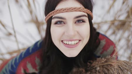 hippi : Close up portrait of a beautiful brunette a boho style hippie girl.The girl looks up and laughs at the camera. Stock mozgókép