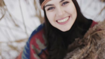 Close up portrait of a beautiful brunette a boho style hippie girl.The girl looks up and laughs at the camera. Stock Footage