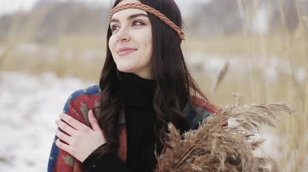 Beautiful brunette girl is walking in a winter day with a bunch of dried reeds in her hands. Stock Footage