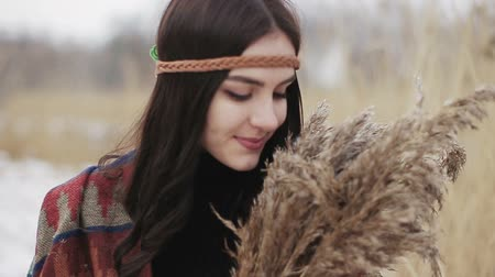 Beautiful brunette girl is walking in a winter day with a bunch of dried reeds in her hands. Dostupné videozáznamy