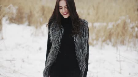 Beautiful brunette girl posing at the camera on a winter day against a background of dry reeds. Dostupné videozáznamy