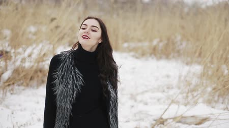 kar taneleri : Beautiful brunette girl smiles and goes to the camera on a winter day on a background of dry reeds.