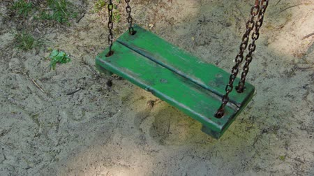 dangle : Old green empty swing.