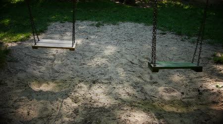 swing : Two empty swings in a playground.