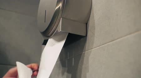 уборная : Hand takes out slowly toilet paper.