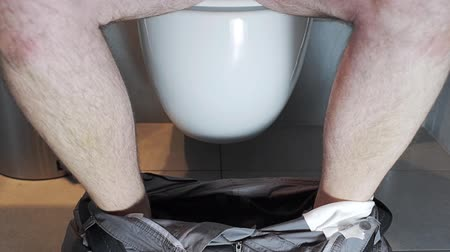 aşağı : Man sits and stand up from a toilet.