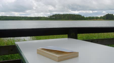 repousante : Book is lying on a table at the lake.