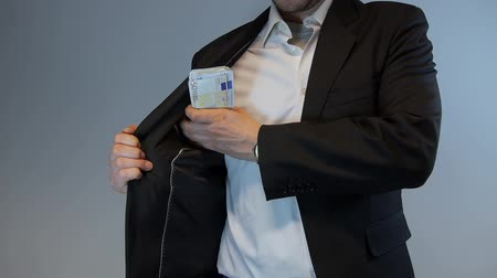 носить : Man in suit hides money into his pocket.