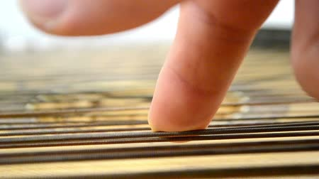 strum : Right hand of unrecognizible man touches shining metal strings. Strings vibrate Stock Footage