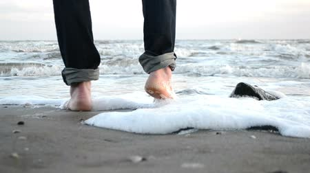 a young man walks barefoot along the sandy shore of the winter sea