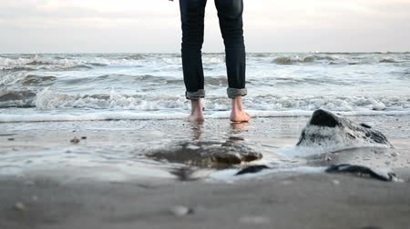 barefooted : a young man walks barefoot along the sandy shore of the winter sea