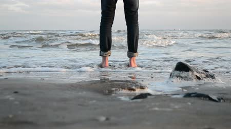 benzer : a young man walks barefoot along the sandy shore of the winter sea